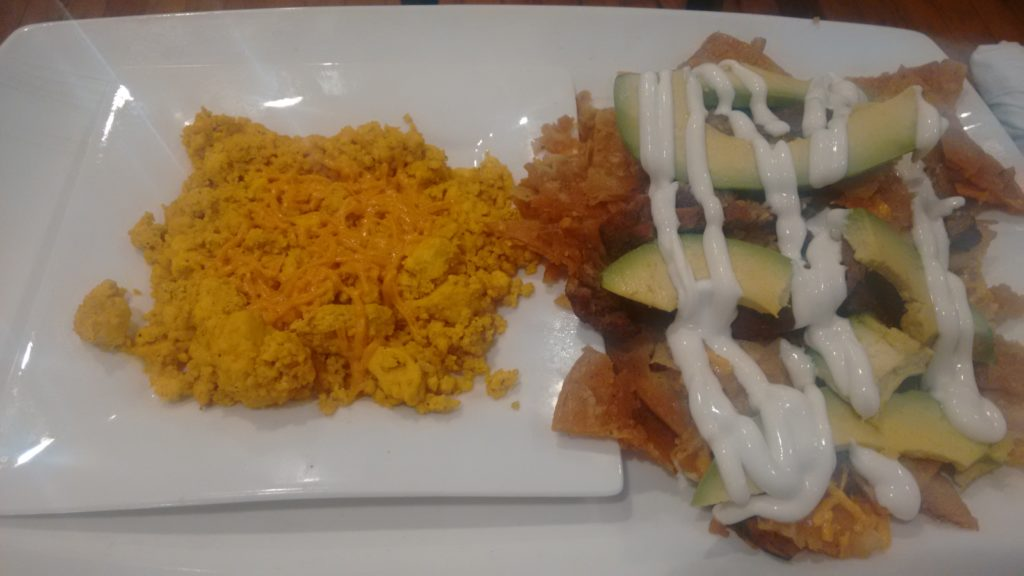 Chilaquiles & tofu scramble topped with vegan cheese